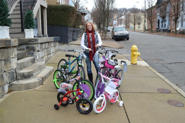 Shannon Hemp-Watson, the executive director of Big Brothers/Big Sisters of the Ohio Valley, collects the six bikes donated for a third consecutive year by Dave and Laura Rotriga, owners of Miklas Meat Market on the corner of Edgington Lane and Carmel Road in Wheeling.