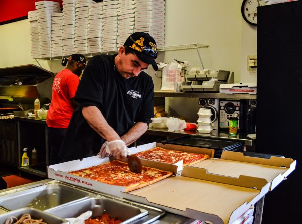 "Employee Jeff Alderman slices ""whole tray"" orders in the downtown Wheeling store."
