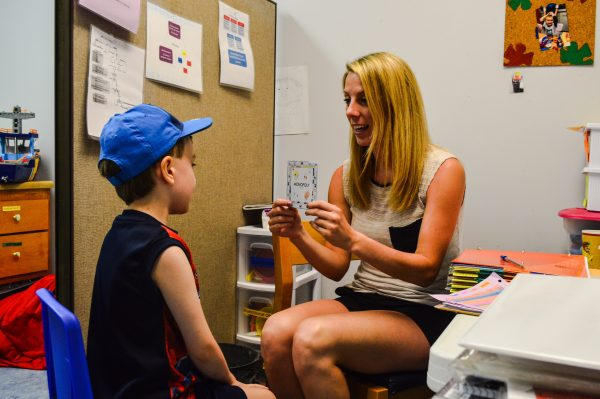 Therapist Olivia Figaretti works on reading and verbal skills with a student.
