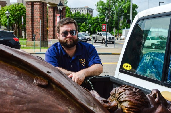 Jeremy Morris, executive director of the Wheeling National Heritage Area Corp., examines the statue before it is placed on the corner of 16th and Market streets.