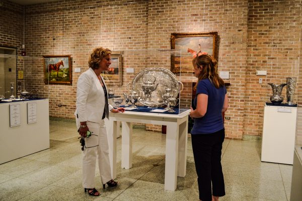 McCracken examines the Oglebay Family Silver Display with Kelsey Traeger, a curator at the Oglebay Mansion.