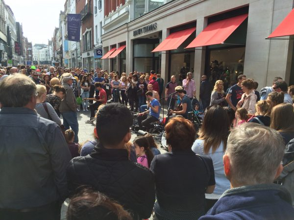 A crowd gathers around a pop-up street performance on Grafton Street in Dublin.