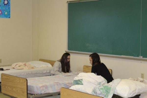 Kaleigh Bryant and Emily Croft worked together setting up beds.