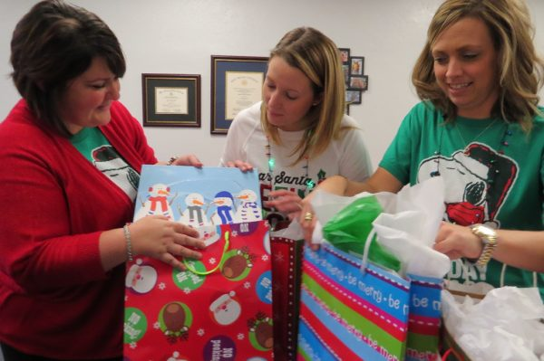 Pictured from left are Bridge Street Middle School Principal Raquel McLeod, teacher Kristy Villani and counselor Heather Lewis as they prepare gifts for one of the school's holiday gift drives.