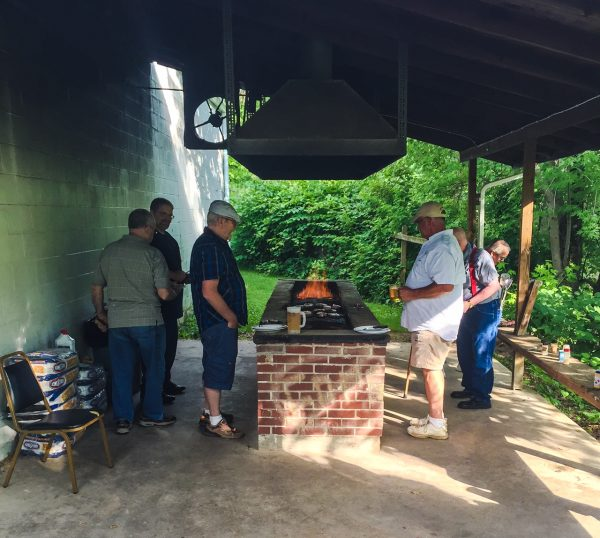 Folks of all ages gather around a facility's pit in order to make their steaks.