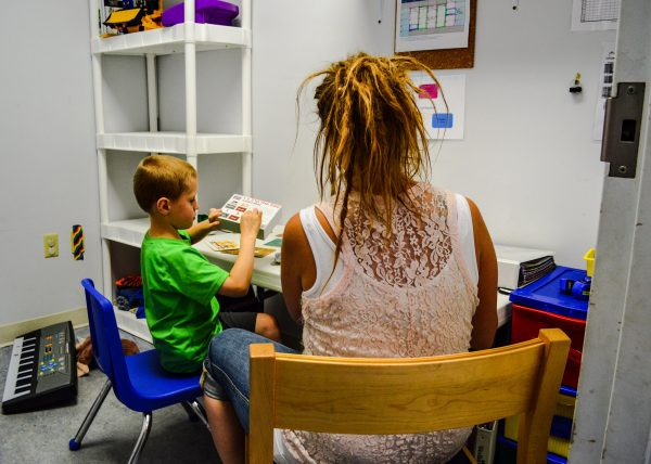 Allison Kolenda, one of several behavior therapists at the center, works on reading with a student .