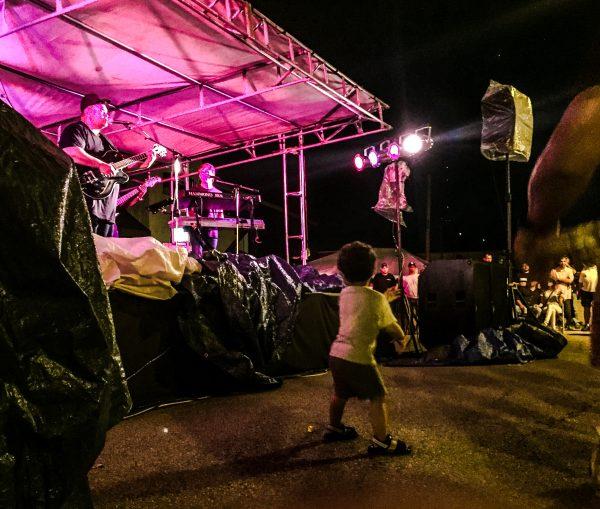 Ezra Hamilton on stage at Wing Fest while his son, Elias, dances.