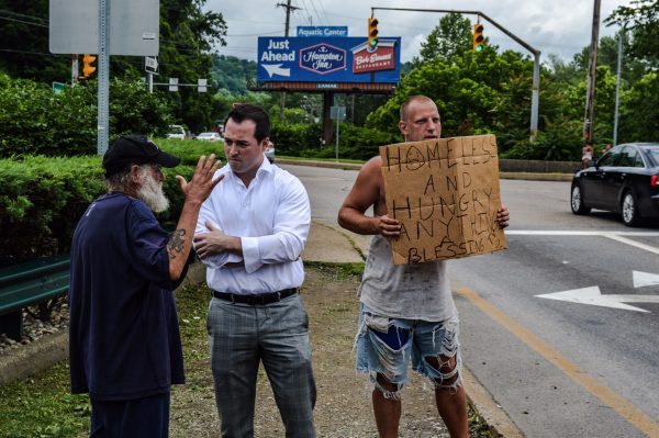 W.Va. Del. Shawn Fluharty speaks with Sonny about his inability to acquire government-issued identification while Bill displays his sign to passing motorists.