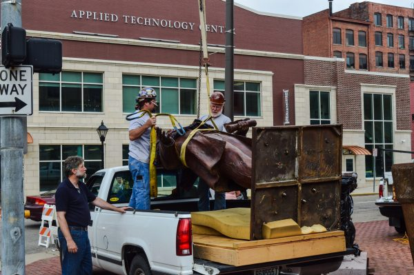 Curtiss helps employees of Walter Construction during the placement of the Pierpont statue on Friday.