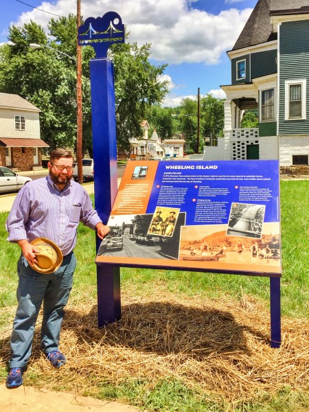 Jeremy Morris, executive director of  the Wheeling National Heritage Area Corp., examines the neighborhood marker on Wheeling Island.