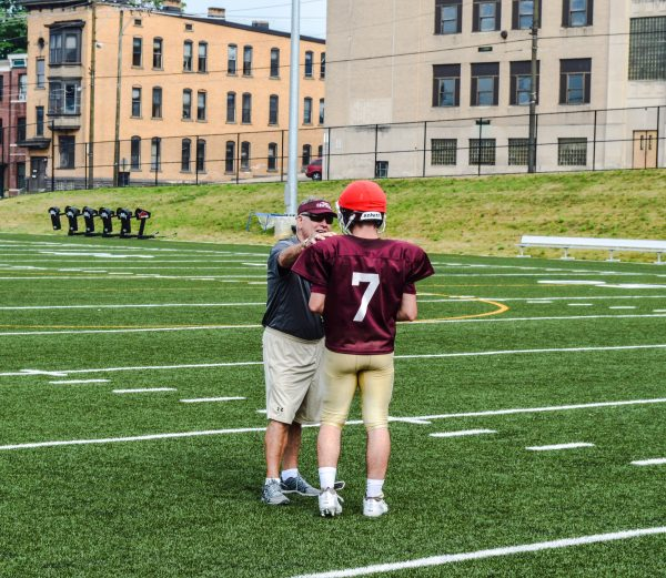 Young speaks with junior quarterback Issac Rine during practice early this week.