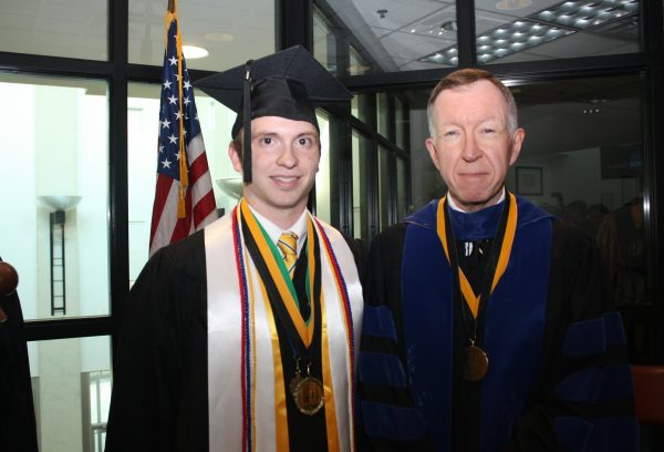 McCollough has been interactive with his students throughout his career, and not much has changed during his third tenure as interim president. Here, he and student speaker Samuel Miller pause to celebrated his commencement.