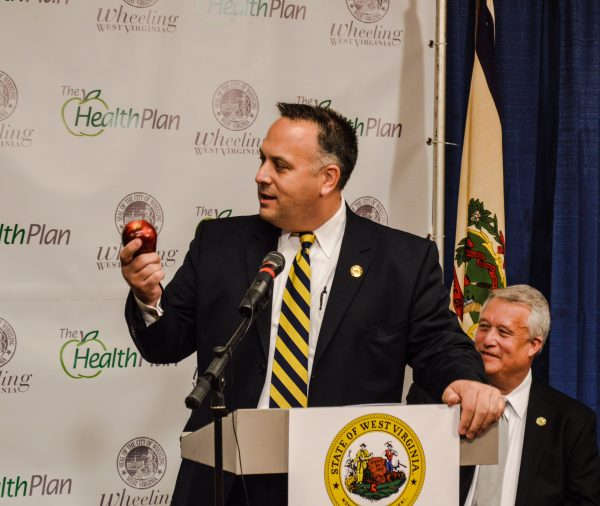 Wheeling Mayor Andy McKenzie presents an apple to Pennington during the press conference.