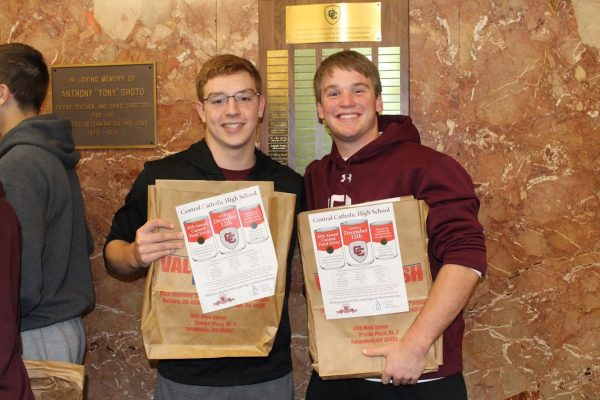 Alec Castello Jochum and Michael Niggemyer helped pass out the 5,000 bags donated by Riesbeck's Food Market.