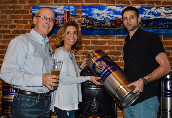 Carl Carenbauer and Erin Ball from Carenbauer Distributing accept on of the new kegs that will utilized for distribution.