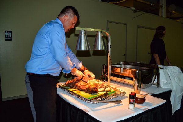 Jason Miller, one of two owners of River City Restaurant and Banquet Center in downtown Wheeling, carves the prime rib for a recent wedding reception.