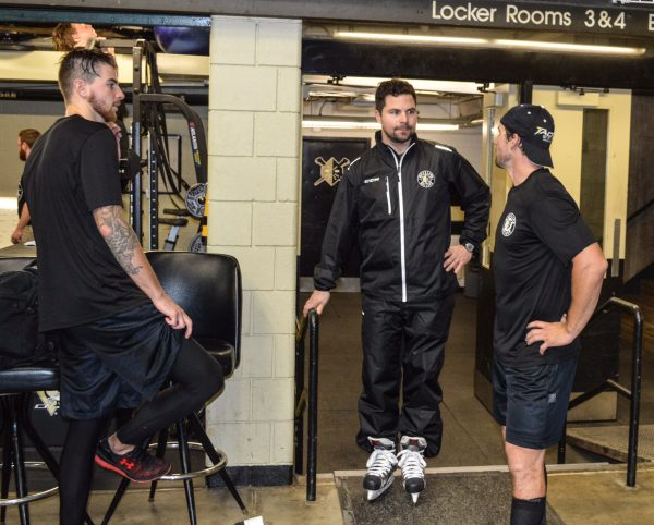 Assistant Coach Riley Armstrong speaks to a couple of players during training camp.