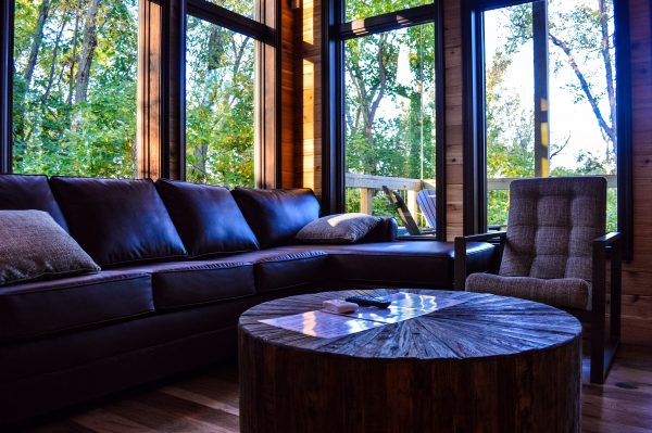 The living room areas of the treehouse cabins are surrounded by nature that visitors will enjoy no matter what the weather may offer on the other sides of the many windows.