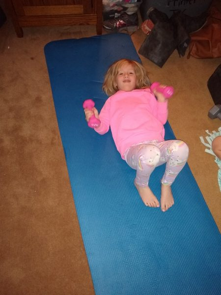 little girl on yoga mat with weights